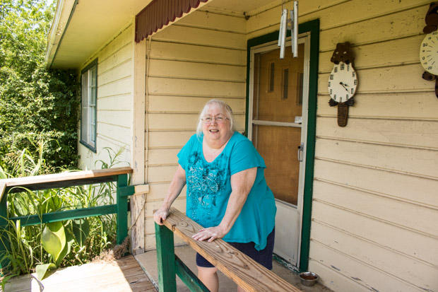 Susan Holmes stands on the front porch of her home in Bokoshe, Okla.