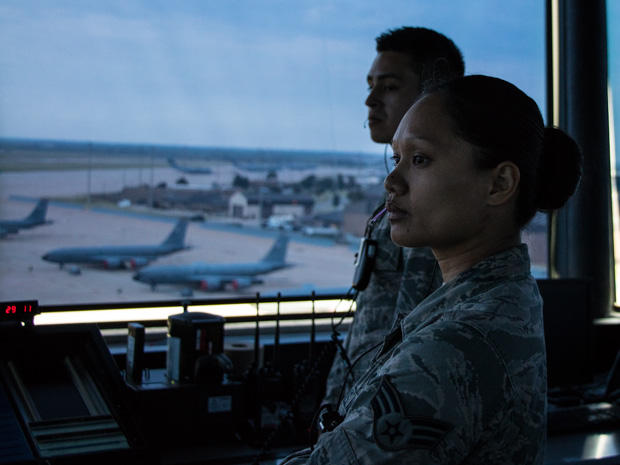 Trainees in the control tower at Altus Air Force Base watch as a C-17 cargo plane taxis to the runway.