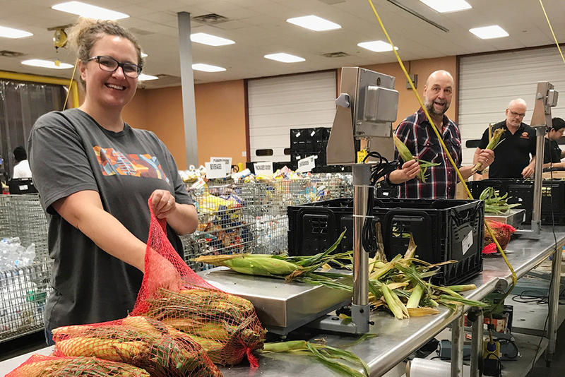KOSU's Jenny Mae Harms, John Cooper and Kelly Burley sort and pack corn at the Community Food Bank of Eastern Oklahoma in August.