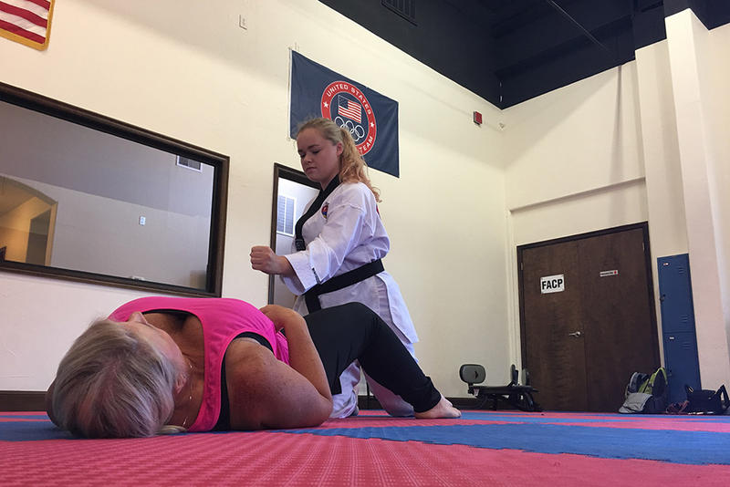 "Poos Taekwondo Instructor Alex Mitchell pretends to make a strike at domestic violence survivor Sandra ""El"" Elrod during a class intended to teach self-defense to women."