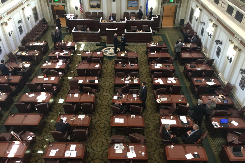 Several legislators mill about nearly fourty minutes after voting on HB1035 opened. Despite holding the vote open, the bill failed to get the needed 75 percent of the votes to pass.
