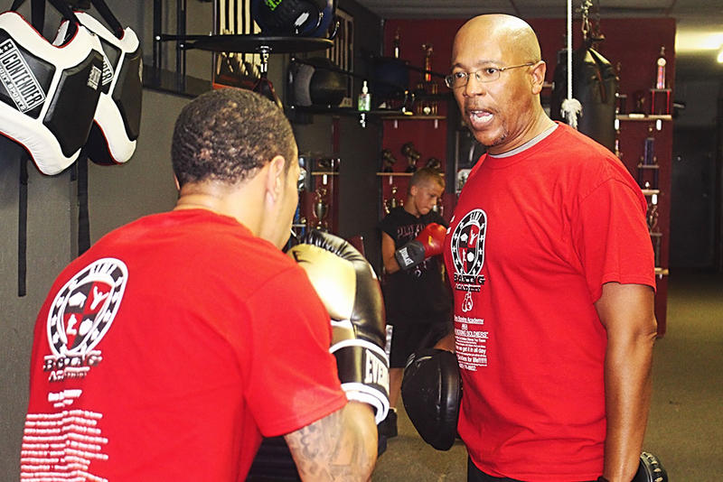 """Marcus McMinn (""""Coach Mac"""") trains a young boxer at his southeast Oklahoma City boxing club."""