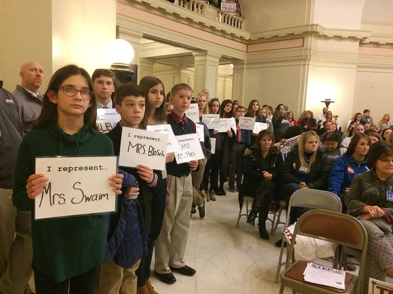 Students hold signs with their teacher's names on them, calling for lawmakers to pass the Step Up Oklahoma plan and give their teachers raises.