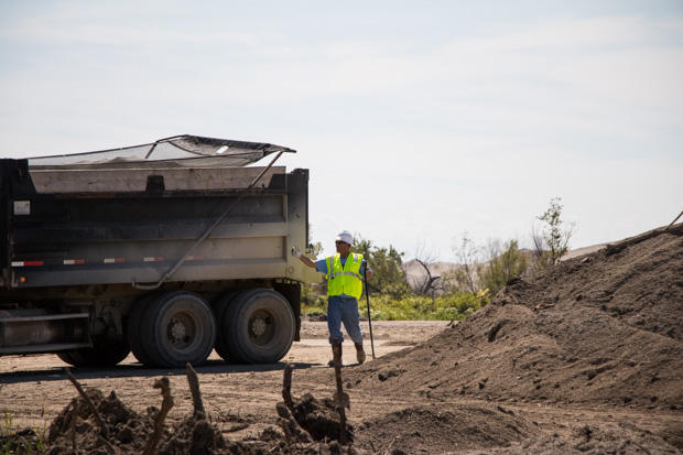 A worker brushes dusty mine waste off a truck before it exits a field at the Tar Creek Superfund in northeastern Oklahoma.