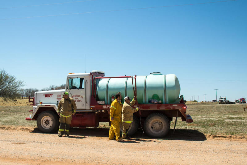 Firefighters man a tanker truck at a wildfire near Waynoka, Okla.