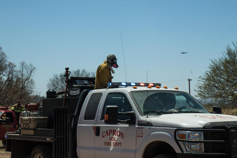 Firefighters return as a helicopter prepares to drop water at a wildfire near Waynoka. Okla.