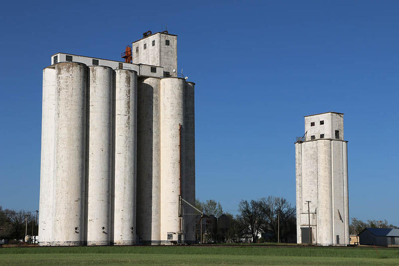 The smaller 60,000-bushel elevator at Goltry, Oklahoma, seen on right, was Tillotson Construction Company's first reinforced-concrete grain elevator, built in 1939.