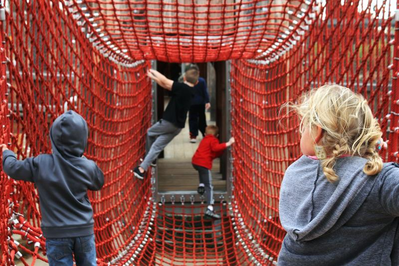 Kids make their way across a net bridge at the Gathering Place in Tulsa.
