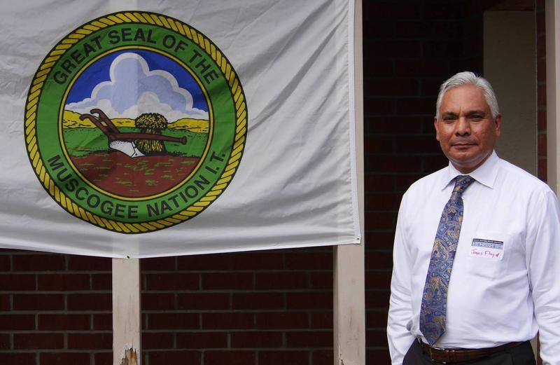 Muscogee (Creek) Nation Principal Chief James Floyd stands beside the nation's flag.
