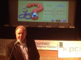 KPCW General manager Larry Warren prepares the audience for the discussion on local aspects of healthcare,
