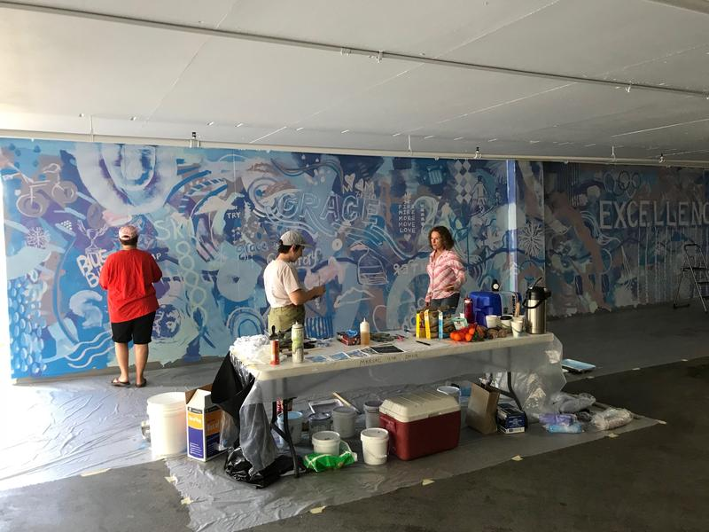 Artist Emily Herr and members of the public helping add the second layer.