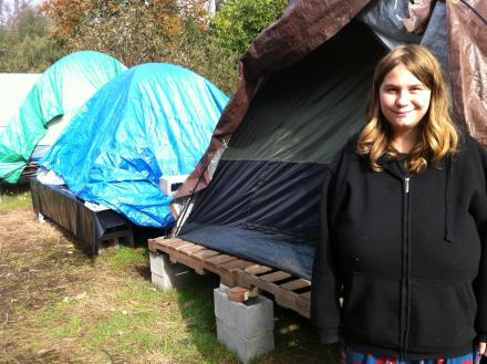 Felicia Leathley stands outside her tent.