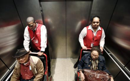 In this Tuesday, Oct. 22, 2013 photo, wheelchair attendants Erick Conley, left, and Sesilia Vaitele assist a pair of passengers heading to an overseas flight at Seattle-Tacoma International Airport, in SeaTac.