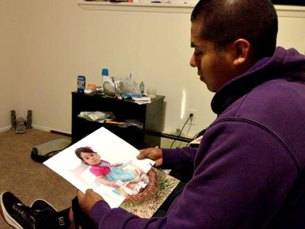 Baggage handler Socrates Bravo looks at a photo of his daughter in his SeaTac apartment.