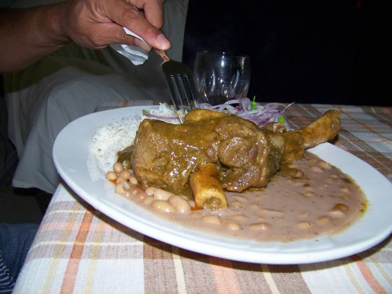 A plate of lamb and hearty white beans is set before hungry customers. This particular Sunday, Lupita made many different dishes including: Roast duck, fresh ceviche, battered fish dishes and a rice pudding and thick fruit sauce.