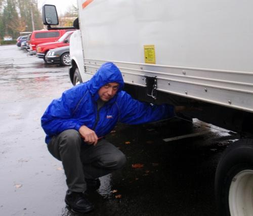 In Olympia, Sergey Kazanchev, manager of the Budget Truck Rental agency, examines the repair on a fuel line sliced by a thief.