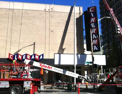Workers place updated signs outside the remodeled Cinerama in downtown Seattle last month. The movie palace reopens tonight for a midnight showing of the latest Harry Potter sequel.