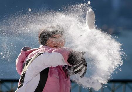 Madie Baker's snowball disintegrates as she throws it at a friend in a downtown park Tuesday, Nov. 23, 2010, in Seattle.