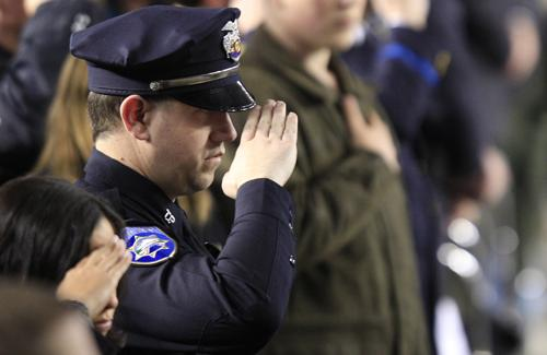 In this photo taken a year ago at the memorial for the four fallen Lakewood Police officers, an officer salutes during ceremonies at the Tacoma Dome on Dec. 8, 2009.
