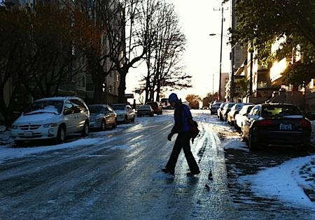 A woman walks gingerly across icy Boylston Avenue on Seattle's First Hill Tuesday morning. The street had a thick layer of compact snow and ice, like many in the region.
