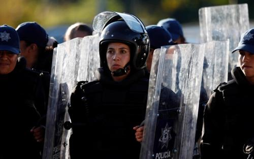 Riot police stand in formation outside the United Nations Climate Change Conference in Cancun, Mexico, Sunday Dec. 5, 2010.