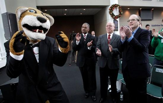 "Microsoft co-founder Paul Allen, right, Scott Carson, center, and Washington State University president Elson Floyd applaud with the WSU mascot ""Butch"" in Seattle on Dec. 2, 2010."