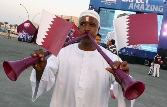 A Qatari man displays the national flag and blows on a vuvuzelas, at Doha souk where people gathered to hear FIFA's selection on World Cup sites for 2018 and 2022, Dec. 2, 2010. Qatar won the 2022 bid.