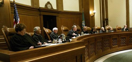 Washington Supreme Court justices listen to arguments during a court hearing.