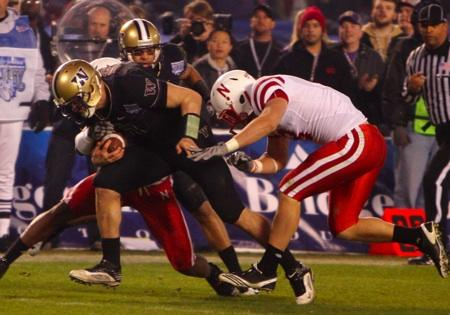 Washington quarterback Jake Locker breaks through two Nebraska defenders while running 25 yards for a touchdown during the second half of the Holiday Bowl game in San Diego, Thursday, Dec. 30, 2010. Washington won 19-7.