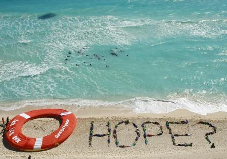 Greenpeace activists form the word hope as a question with their bodies, next to a giant life saver, during a demonstration near the site of the United Nations Climate Change Conference in Cancun, Mexico, Friday, Dec. 10, 2010.