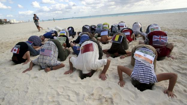 Seattle students Ian Siadak and Lauren Ressler are among the more than 20 Sierra Club activists wearing national flags and hiding their heads in the sand near the U.N.climate summit in Cancun, Mexico.