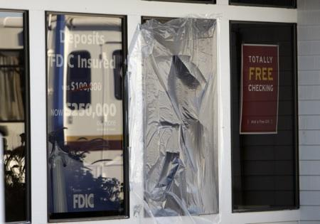 A taped over window is seen at West Coast Bank Monday, Dec. 15, 2008, in Woodburn, Ore. A father and son have been convicted in the deaths of two police officers who were killed when the bomb exploded.