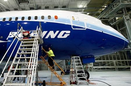 A worker climbs aboard a 787, the first of the model scheduled to fly, at the plant in Everett, Wash, in April 2009. Company officials have announced another delay in the first delivery of the new plane, an event postponed to July.