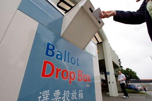 A voter drops an absentee ballot into a collection box
