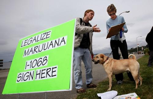Vicki Sessions, right, stops on her jog with dog Solli to sign a marijuana legalization petition for volunteer Terren Dubuque Thursday, July 1, 2010, in Seattle. The petition failed to get enough signatures.  Backers will try again this year.