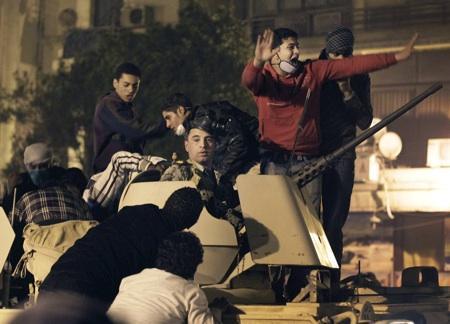 An Egyptian Army soldier riding in an armored vehicle is surrounded by anti-government protesters near Tahrir square in Cairo, Egypt, Fri., Jan. 28, 2011. Seattle is one of a few US cities with weekend rallies supporting the protests.