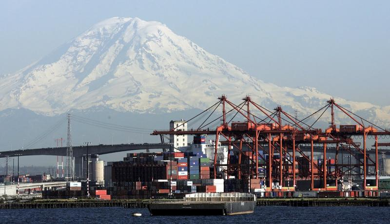 Snow-capped Mount Rainier looms behind cranes and stacked cargo containers at the Port of Seattle