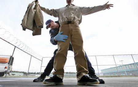 Correctional officer Ken Kleinworth frisks an inmate leaving a dining hall at the Washington Corrections Center in Shleton last Thursday. The population of Washington state prison inmates has become whiter, older and more violent in the past decade.