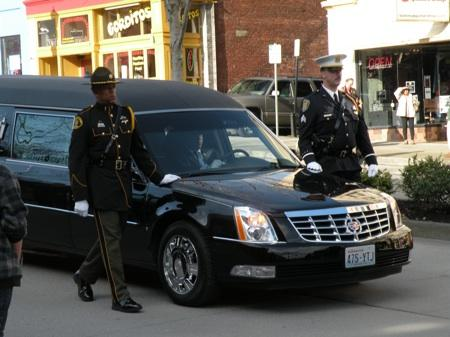 Uniformed officers escort the hearse carrying the body of slain Corrections Officer Jayme Biendl to a memorial service at Comcast Arena in Everett Tuesday.