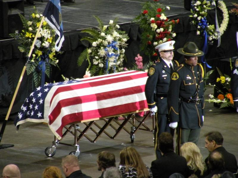 An honor guard stands before the flag-draped casket bearing the body of Corrections Officer Jayme Lee Biendl during a memorial service held Tuesday at Comcast Arena in Everett. Biendl's family sits in the front row.