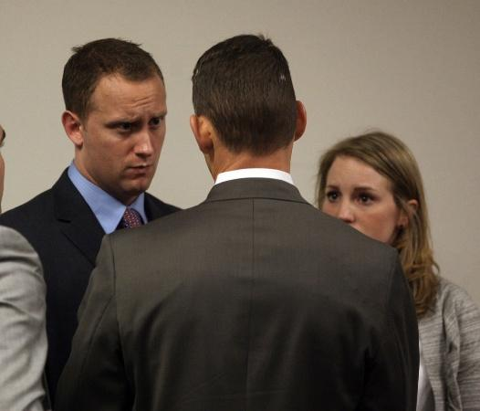 Seattle Police Officer Ian Birk, left, and his wife Camille Birk talk with Birk's attorney Ted Buck during the coroner's inquest jury verdict on Thursday, Jan. 20, 2011 in Seattle.