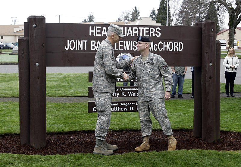 Army Col. Thomas Brittain, (r), and Air Force Col. Kenny Weldon, (r), shake hands upon the merger of Fort Lewis and McChord Air Force Base into Joint Base Lewis-McChord in Feb. 2010.