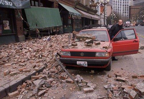 In this 2001 photo, Paul Riek checks to see if his car starts after parts of the top half of a nearby building fell on it, during the Nisqually earthquake.