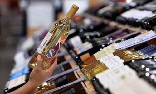 A shopper holds up a bottle of wine from a large selection at a Costco warehouse store.