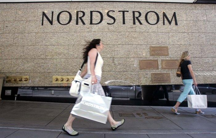 "Shoppers carry bags past the downtown Seattle Nordstrom store. The company announced on Thursday that it's buying the high-end ""flash sale"" website HauteLook."