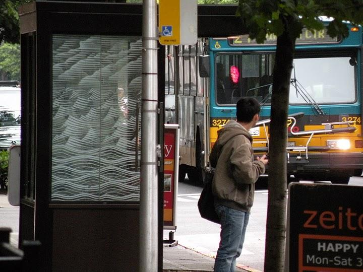 Waiting for public transit Metro bus in downtown Seattle on 4th Avenue.