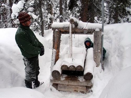 Wildlife biologists John Rohrer (left) and Scott Fitkin check a wolverine trap in Washington's North Cascades