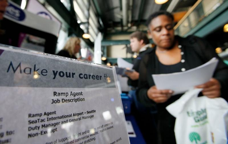 A few more of us are finding work, according to the latest employment figures released by the state's Employment Security Department on Tuesday. This woman is looking for opportunities at a job fair in Seattle.