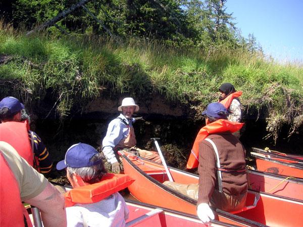UW Brian Atwater (center) points out evidence of the 1700 Cascadia earthquake and tsunami to field-trip participants during a canoe trip along the Niawiakum River.