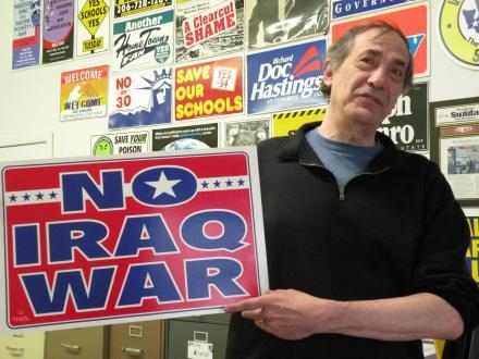 Art Boruck in his print shop, March 2011, holding the sign he designed before the start of the Iraq war.